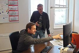 Zwei Mitarbeiter beim Orojektmanagement vor dem Computer.